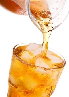 白い背景で隔離の瓶から氷とアイスティーをガラスに注ぐ