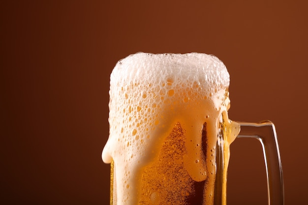Pouring lager beer in glass mug over brown background