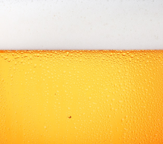 Разлив светлого пива с пузырьками и пеной в морозном стекле