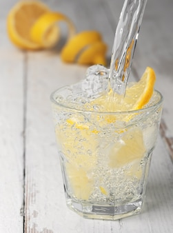 Pouring lemonade into a glass with ice, white wooden vintage background.
