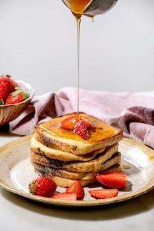 Заливка кленового сиропа из керамического кувшина на запас французских тостов со свежей клубникой на тарелке и розовой тканевой салфеткой над белым столом. домашний завтрак