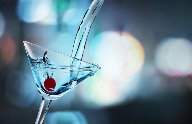 Заливка коктейля мартини в стакан на размытом фоне