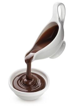 白い背景で隔離の溶けたチョコレートを注ぐ