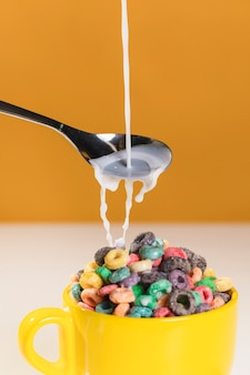 Pouring milk over bowl with cereals