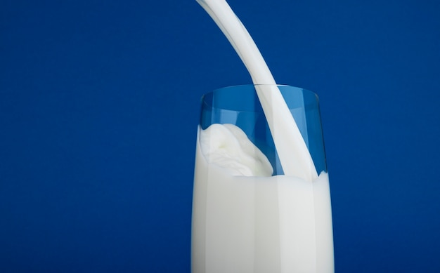 Pouring milk in glass isolated on blue background