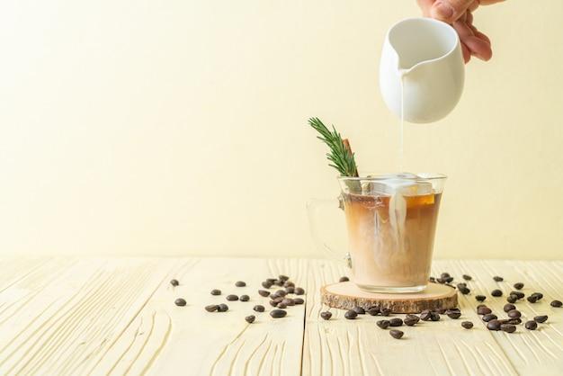 Наливание молока в черный кофейный стакан с кубиком льда, корицей и розмарином на деревянный стол
