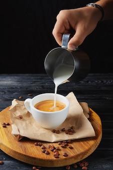 Заливка молока в кофе. чашка с капучино на деревянной тарелке