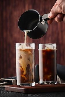アイスコーヒーに牛乳を注ぐ