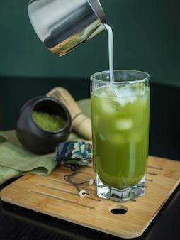 Залив молока в стакан зеленого чая матча со льдом