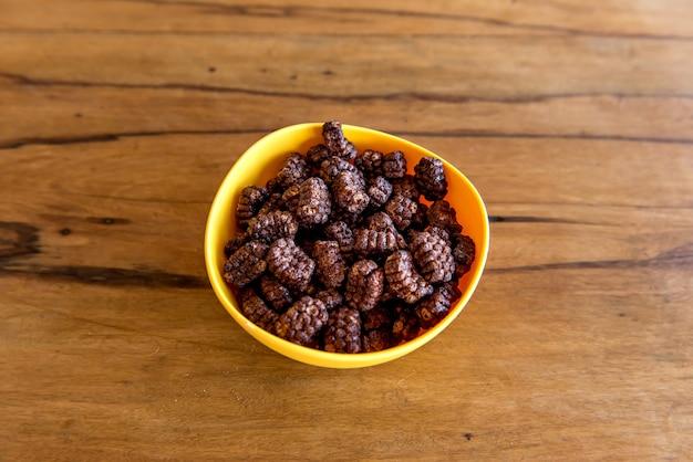 チョコレートコーンフレークボールにミルクを注ぐミルクとコーンフレークと一緒に朝食。