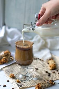 Наливая молоко в кофе