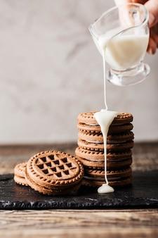 Наливание молока на стопку шоколадного печенья