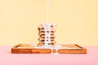 Pouring milk on cookies stack on wooden board