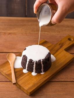 Лить молочный соус на шоколадные пирожные на деревянной тарелке и деревянном фоне. домашняя выпечка и десерт