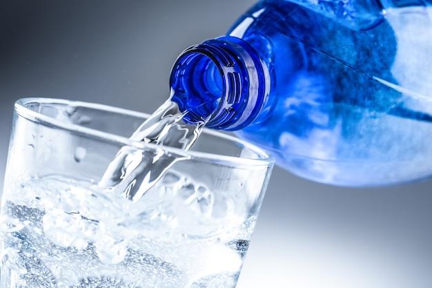 Заливка минеральной воды из синей бутылки в прозрачное стекло на абстрактном сером фоне.