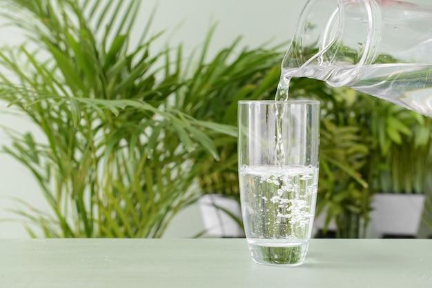 Налив пресной воды в стакан на столе