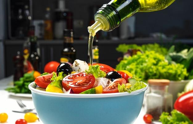 新鮮な野菜サラダ、地中海料理、ギリシャ風サラダ、ヘルシーな食材を添えた白いテーブルにオリーブオイルを注ぐ