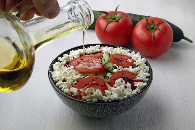 Заливка оливковым маслом салат из свежих помидоров и огурцов