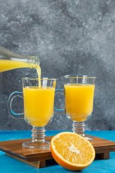 Pouring orange fresh juice in a glass cup.