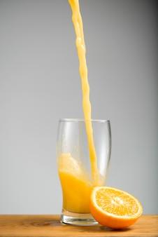 Versare il succo d'arancia nel bicchiere