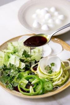 Поливание тыквенным маслом свежих зеленых сырых овощей и зелени, спагетти цуккини, белой редьки, зеленого перца, ледяного салата, шариков моцареллы для приготовления салата. керамическая тарелка на белом мраморном столе.