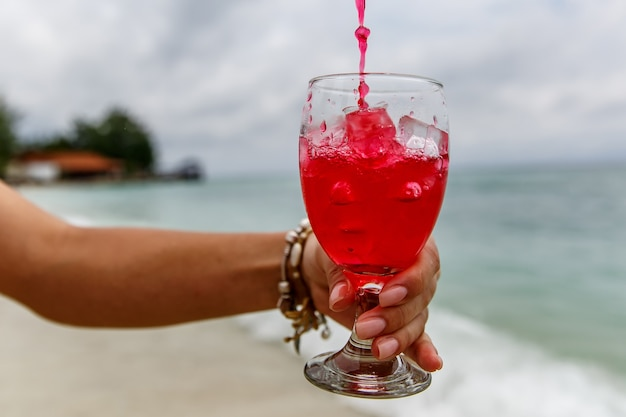 Pouring red soda beverage on summer beach.