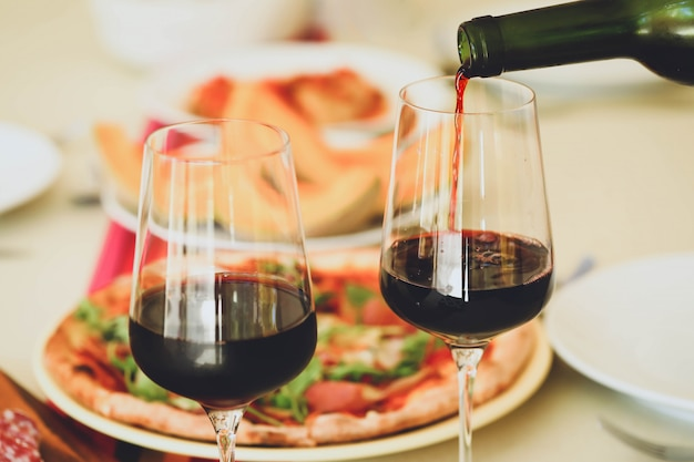 Pouring red wine from bottle into  glasses on table with food background