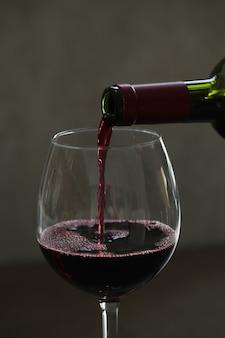 グラスに赤ワインを注ぐ