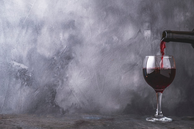 Pouring  red wine into glass on gray wall. copyspace