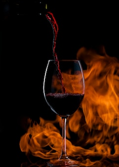 Pouring red wine into glass with long stem, with fire in the background
