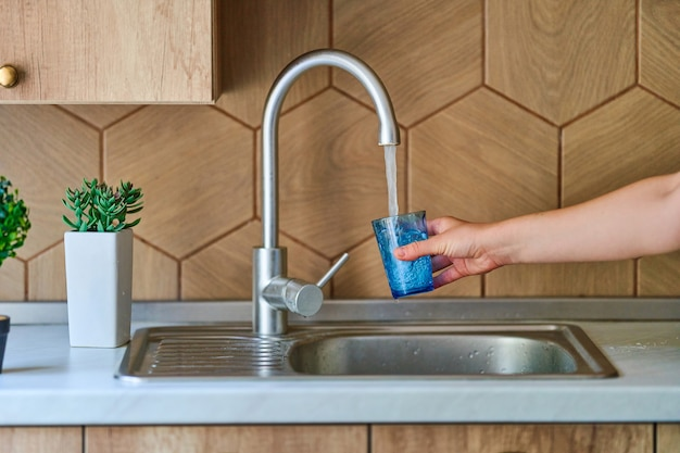 Pouring running purified filtered tap water in glass at kitchen for healthy drinking