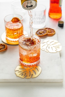 Pouring soda water from a can to make italian aperol spritz cocktail. portrait orientation