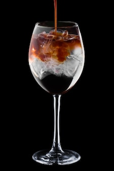 Pouring spresso in cocktail with tonic in wine glass isolated