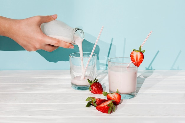 Pouring strawberry yogurt in glasses