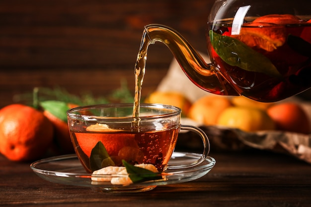 Pouring tangerine tea into cup on wooden