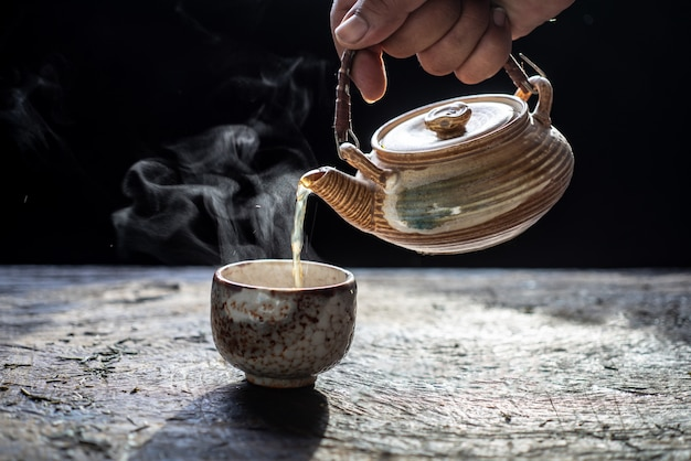 Pouring tea in ceramic teapot and cup with steam on wood background