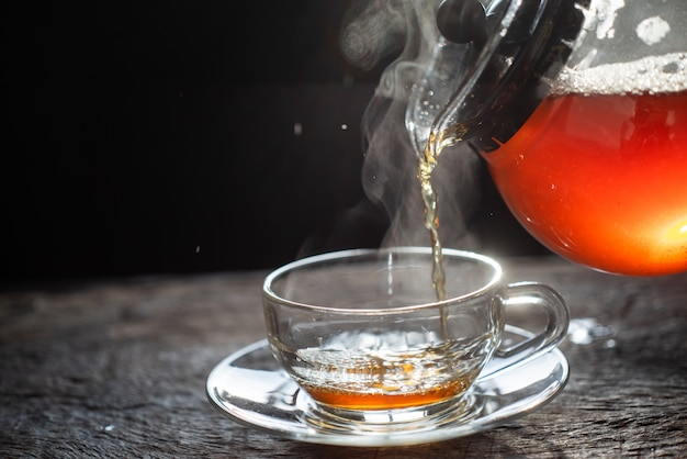 Pouring tea in glass teapot and cup with steam on wood background