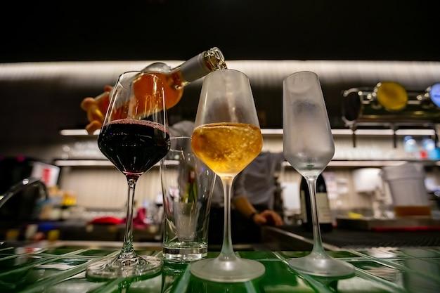 Наливание трех бокалов вина из винной бутылки