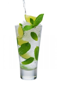Pouring tonic into highball glass with ice crush, mint and lime
