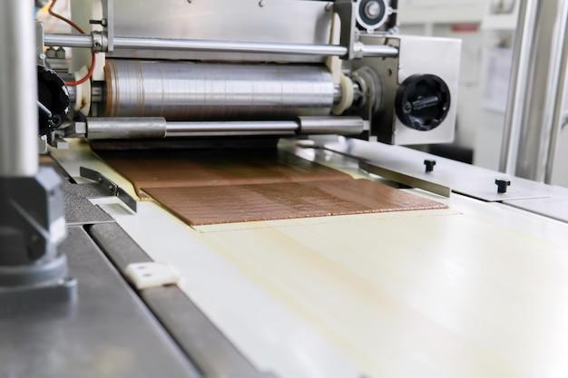 製菓工場のコンベヤーにチョコレートの薄層が入ったウエハースシートを注ぐ