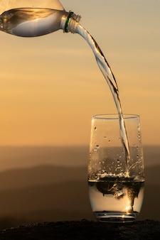 Налив воды из бутылки в чистый стакан с прозрачной питьевой минеральной водой против бактерий ...
