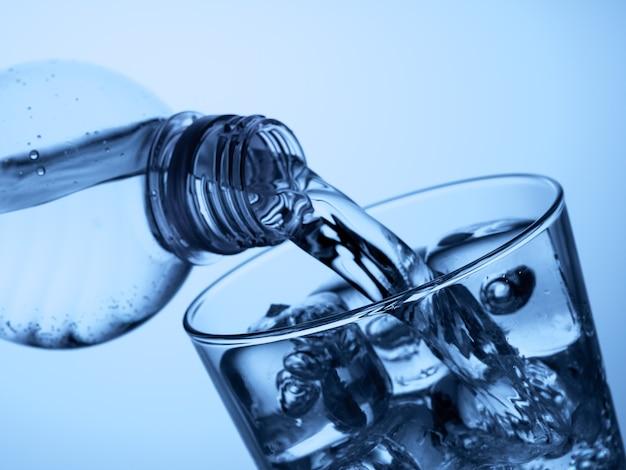 밝은 파란색 배경에 얼음이 있는 유리에 플라스틱 병에서 물을 붓는다