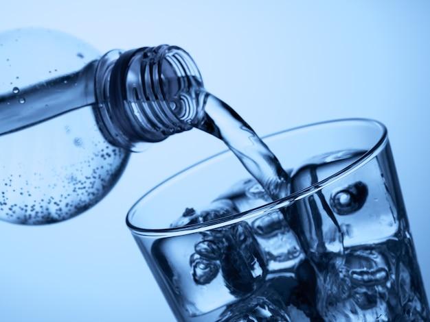 Налив воды из пластиковой бутылки в стакан со льдом на голубом фоне