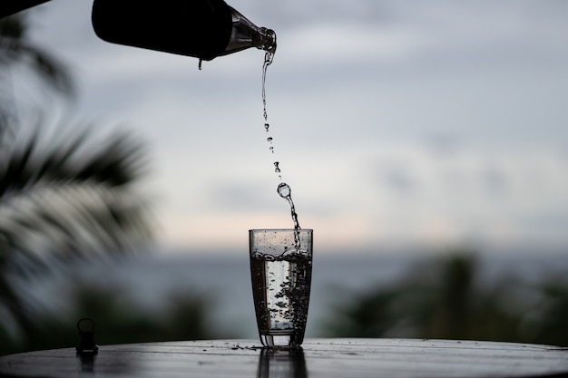 Pouring of water from the bottle in the glass on nature background