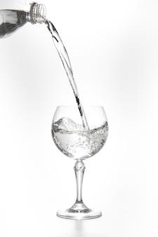 Лить воду из бутылки в стакан на синем фоне