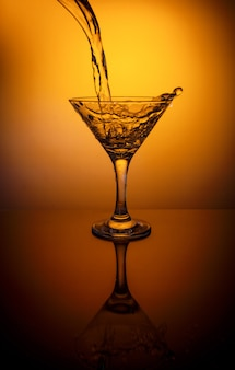 Pouring water from bottle into glass on a thin stalk on orange surface, wineglass with reflection