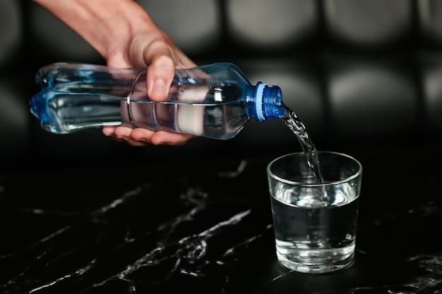 Налив воды в стакан, синяя бутылка с водой