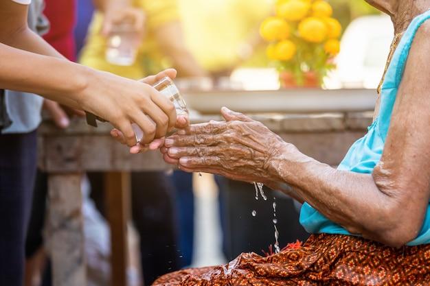 존경받는 장로들의 손에 물을 붓고 송크란 축제에 행복한 축복을 요청하십시오