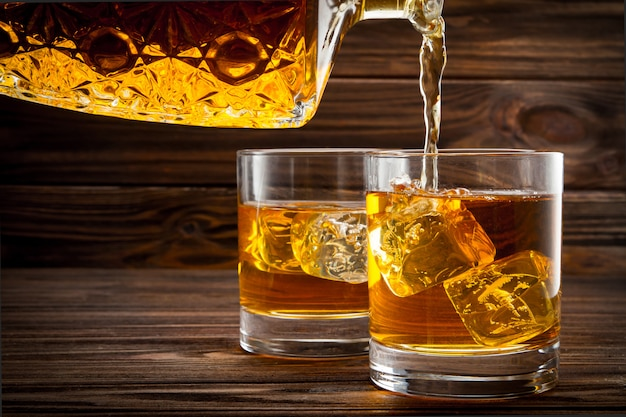 Pouring whiskey from bottle in the glasses
