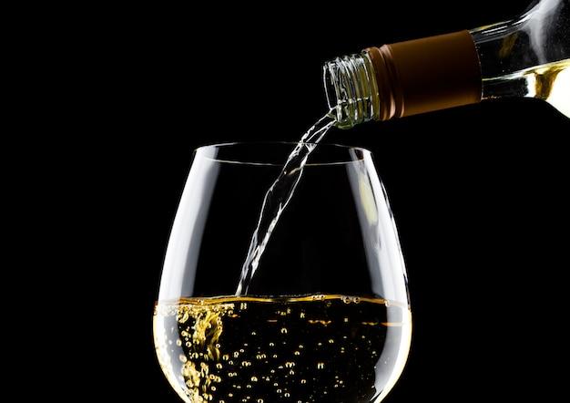 ボトルから分離されたガラスに白ワインを注ぐ